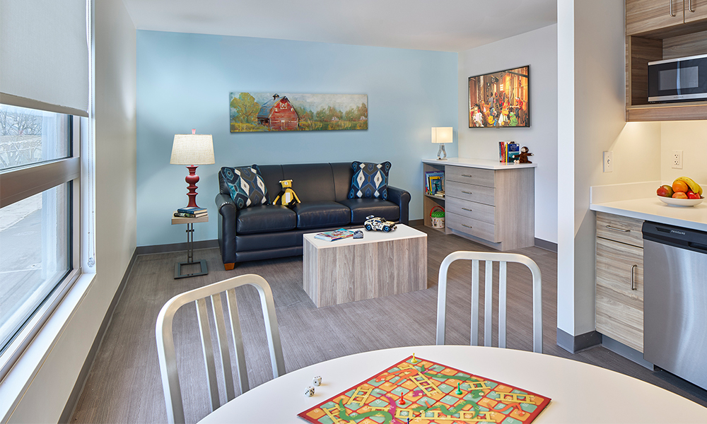 A family living space with a TV room, a full kitchenette and dining table.